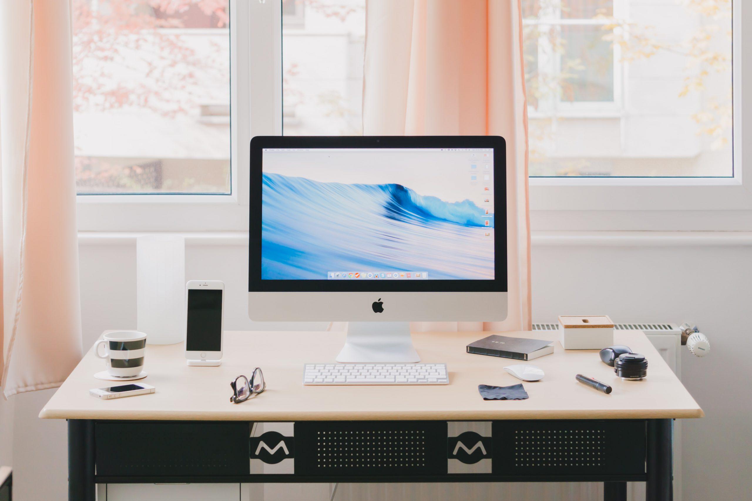 自宅の部屋のデスクの上にあるデスクトップパソコンとメモ帳