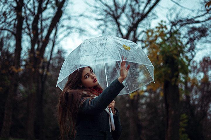 雨の中で傘をさしている女性の写真
