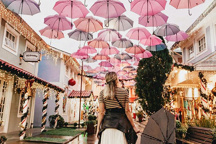 雨の日に傘をさしている女性と大量の傘