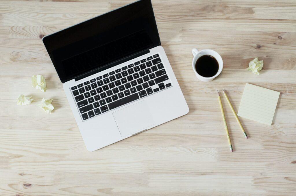 自宅の机にあるコンピューターと筆記用具一式