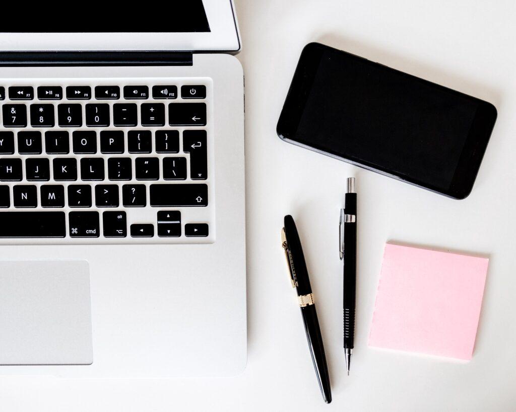 ラップトップ、ペン、スマホ、メモ帳とペンの写真