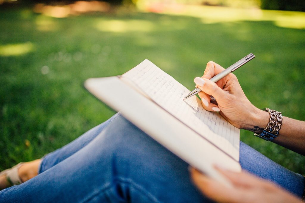 writing with a note and a pen