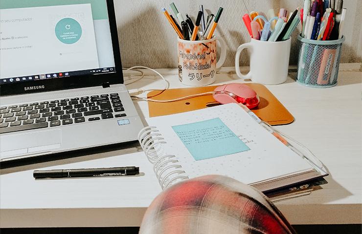 オンラインラーニング用のデスクとラップトップとノートとペン