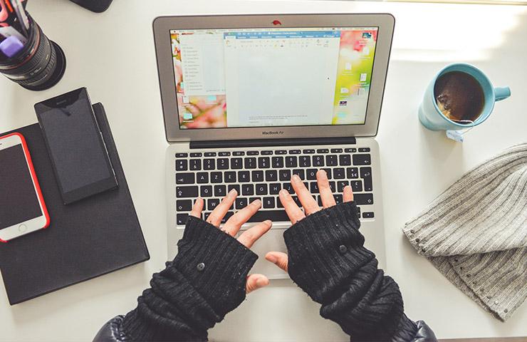 パソコンを使ってWordファイルで論文の執筆をしている女学生