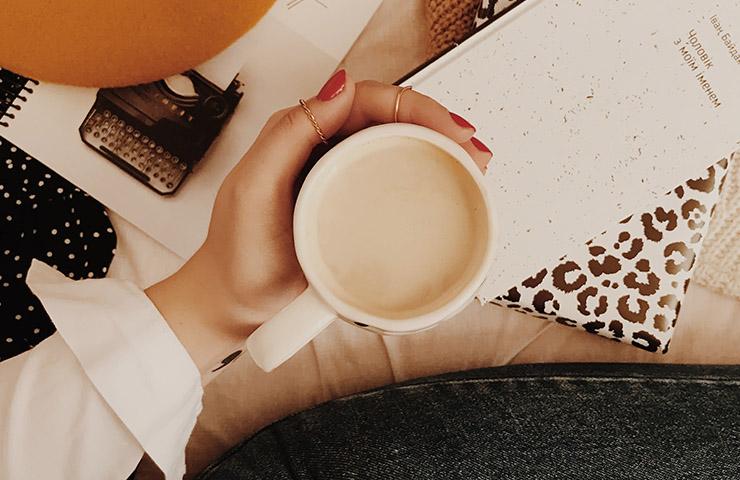 コーヒーを飲みながら本で読書をしている女性