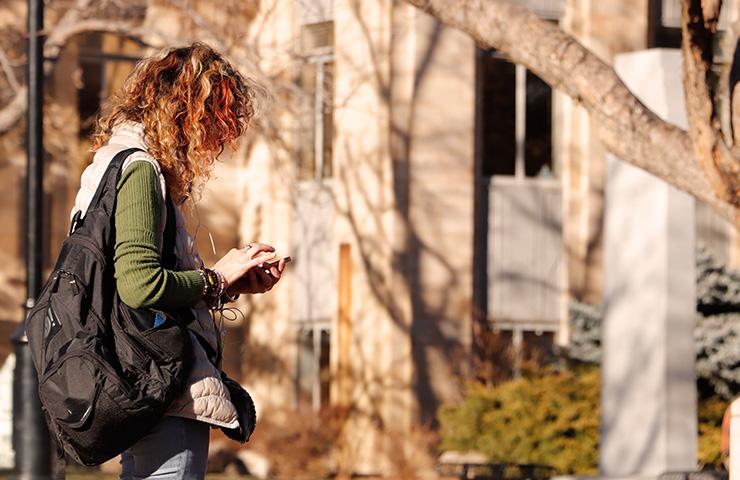 大学のキャンパス前に立っている女子大学生