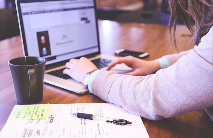 大学でコンピューターで勉強をしている女子大学生