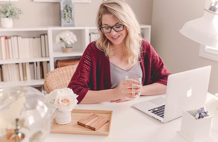 家でコンピューターで勉強している女性