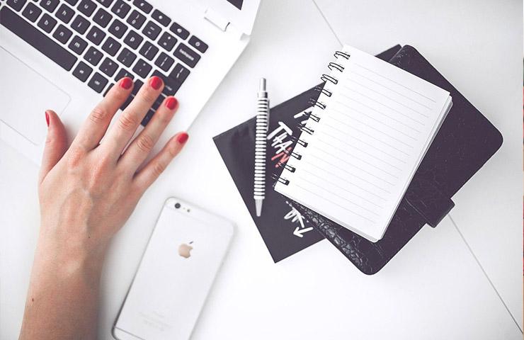 パソコンを使っている女性とノートブック、ペン、スマートフォン