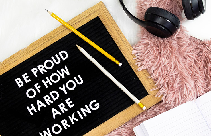「Be proud of how hard you are working」の文字とヘッドフォンとスマホ