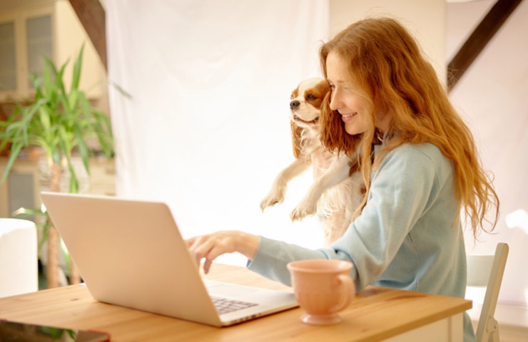 犬と一緒にオンライン英会話レッスンを受講している女性