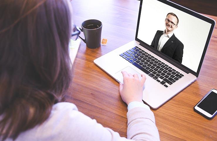 オンライン英会話講師とビデオ通話をコンピューターでしている女性