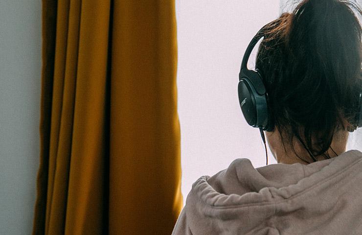 オンライン英会話レッスンをヘッドフォンで受けている女性