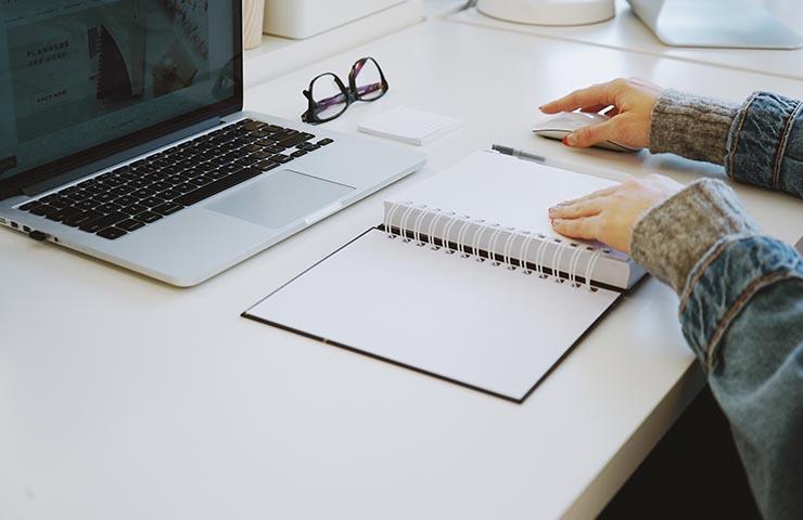 コンピューターとノートブックを使いながらオンラインで学んでいる女性