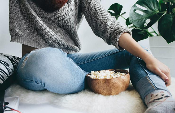 ポップコーンを食べながらTVドラマを観ている女性