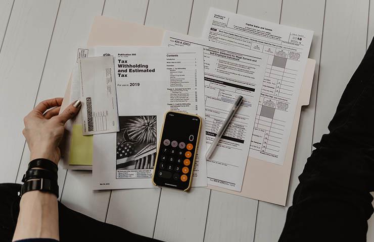 税金やキャピタルなどの書類と計算している女性