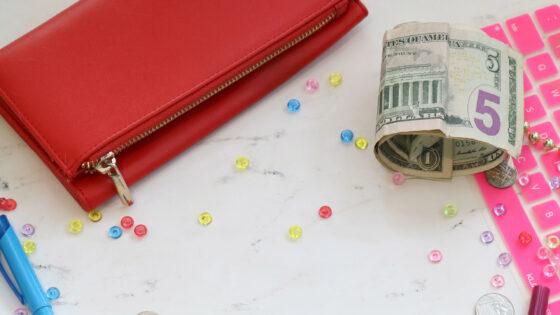 財布とドル札、ミクロ経済学の勉強用のペン、キーボード