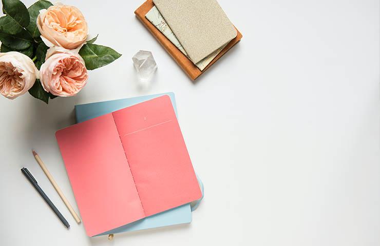 机の上にあるノートブックとペン