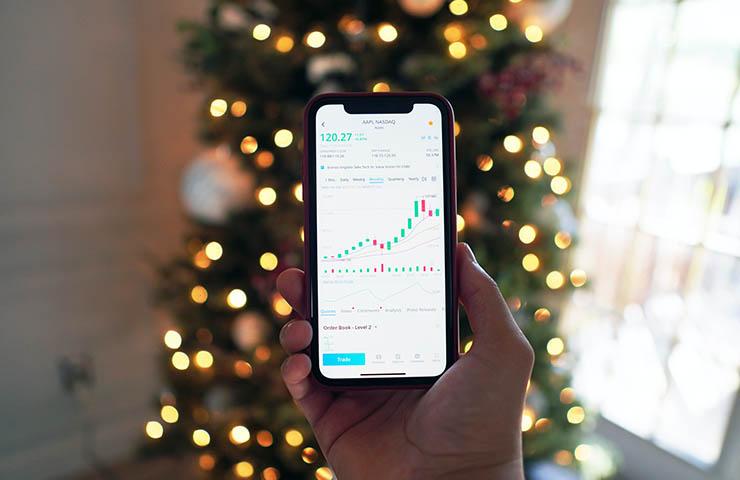 携帯電話の中に映る株式市場チャートの画面