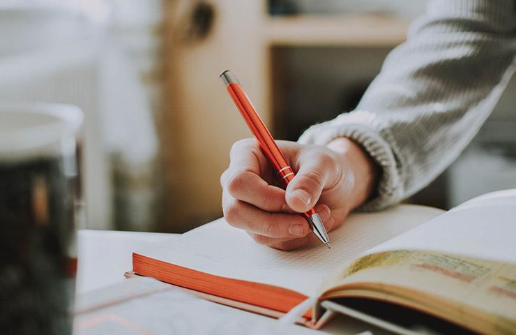 ノートを使って一生懸命勉強している女性