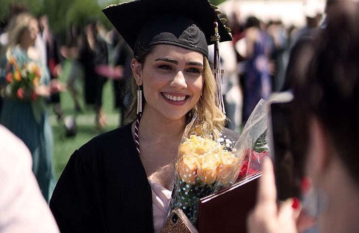 花束を持ってお祝いされている大学生