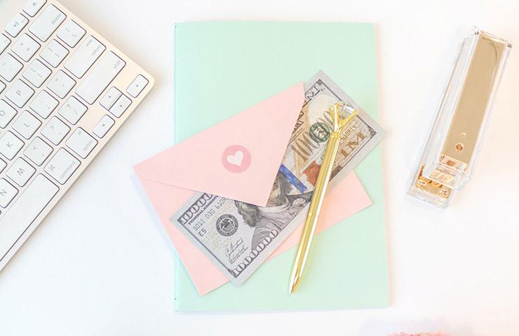 マクロ経済学レビュー用のキーボード、ノート、ペン、米ドル札