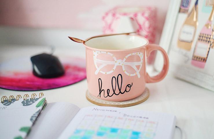 机の上に置かれているマグカップ、スケジュール帳、マウス、ノート