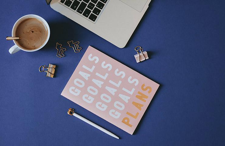 目標プランと書かれたノートとラップトップ