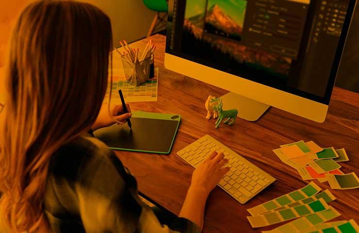 Adobeのイラストレーターで編集している女性