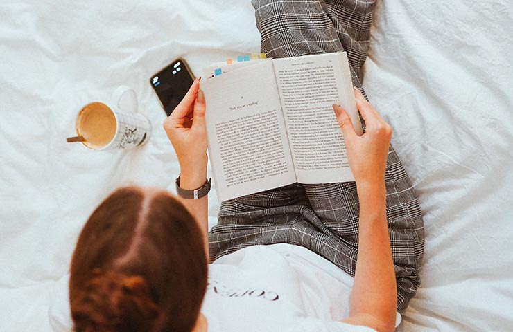 教材を読んでいる女子大学生