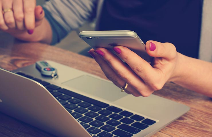 問い合わせのために電話とコンピューターを使っている女性